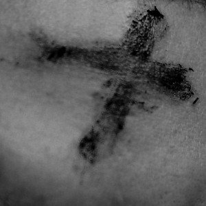 Cross in ashes on human skin