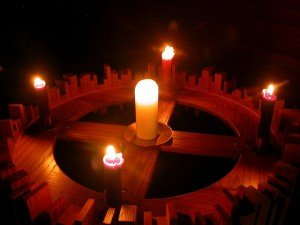 Lit candles in a wooden Advent wreath stand