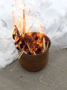 Palms burn in a canister next to a snow bank